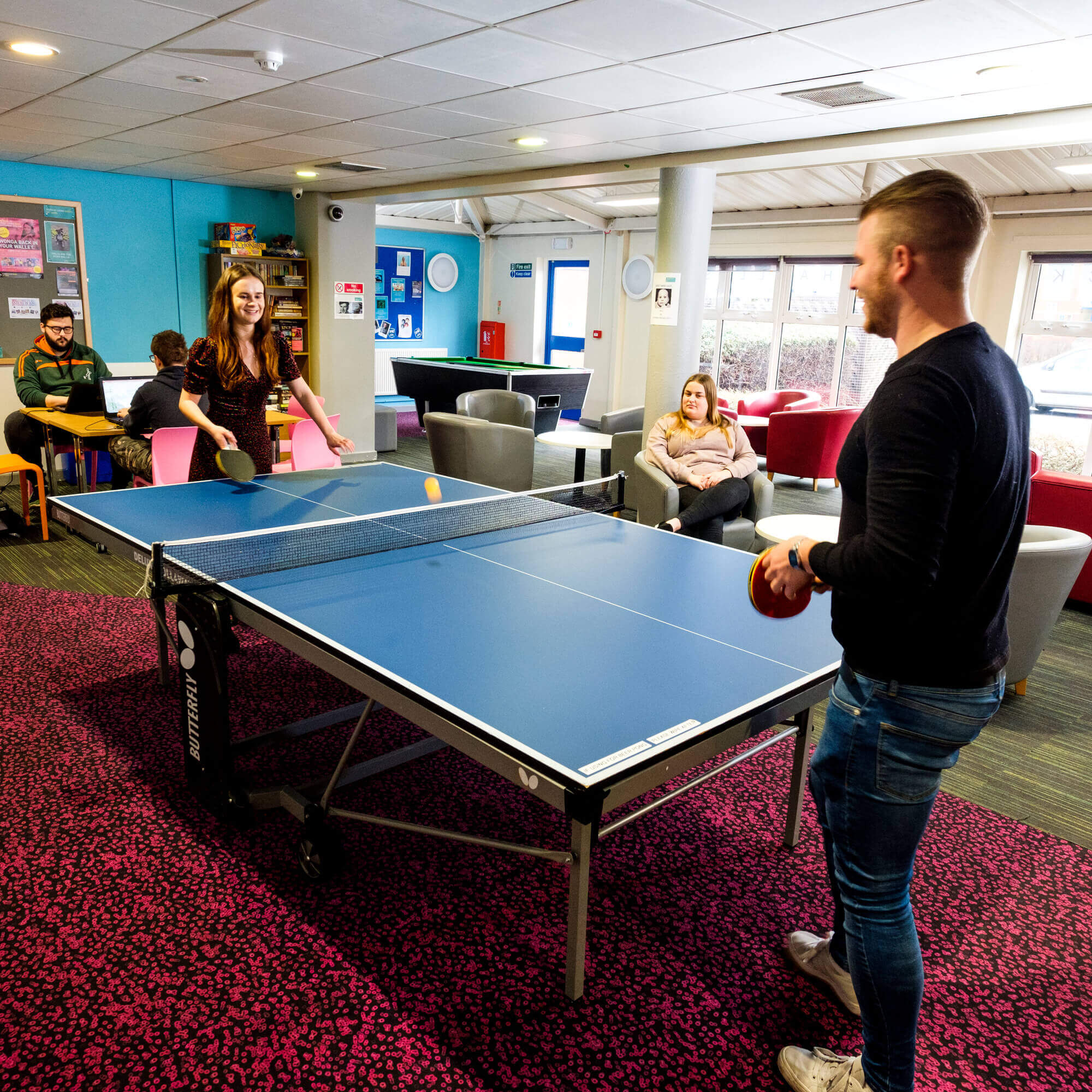 Two students playing table tennis in halls common room