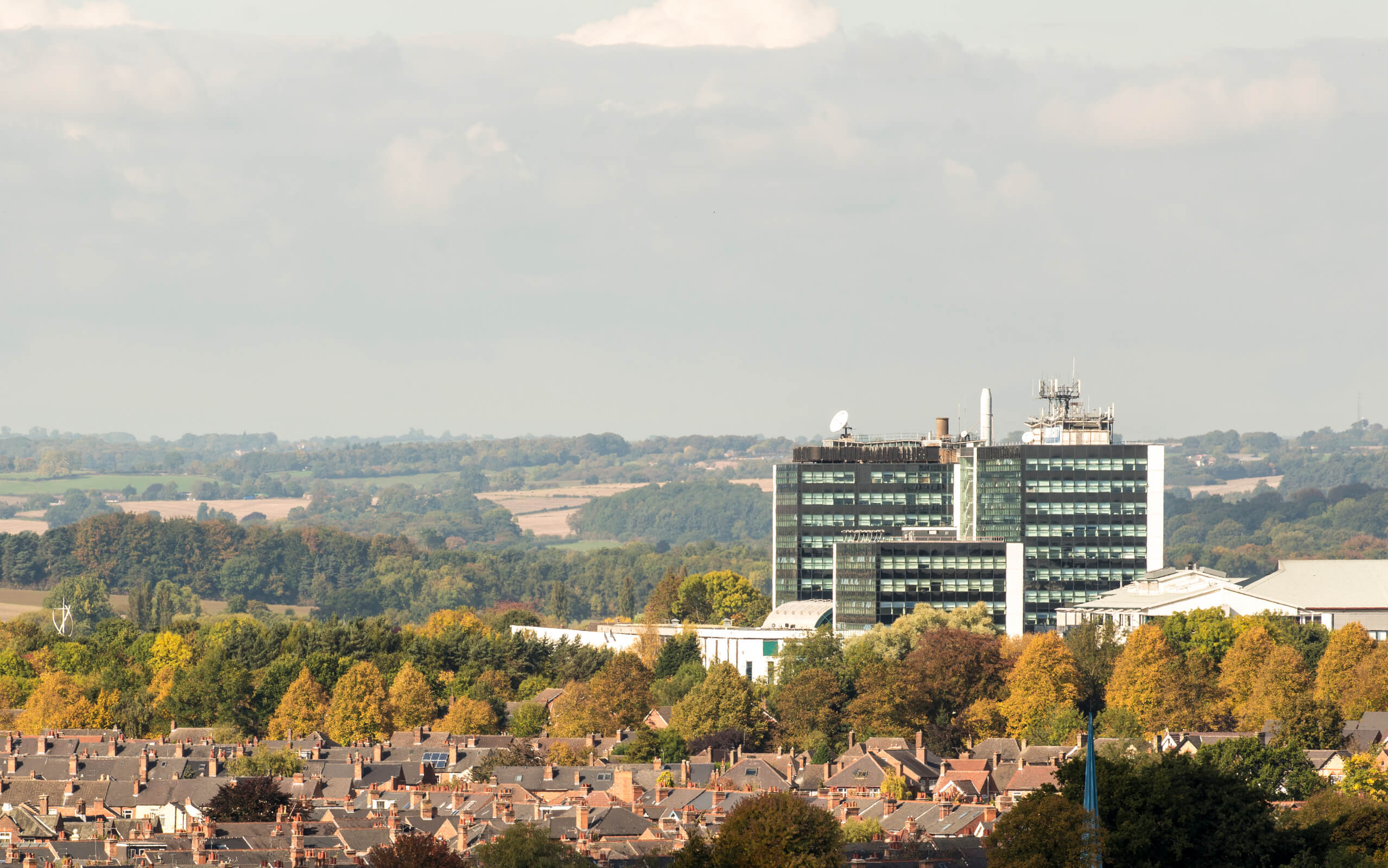 A wide landscape shot of Derby with the University building and greenery