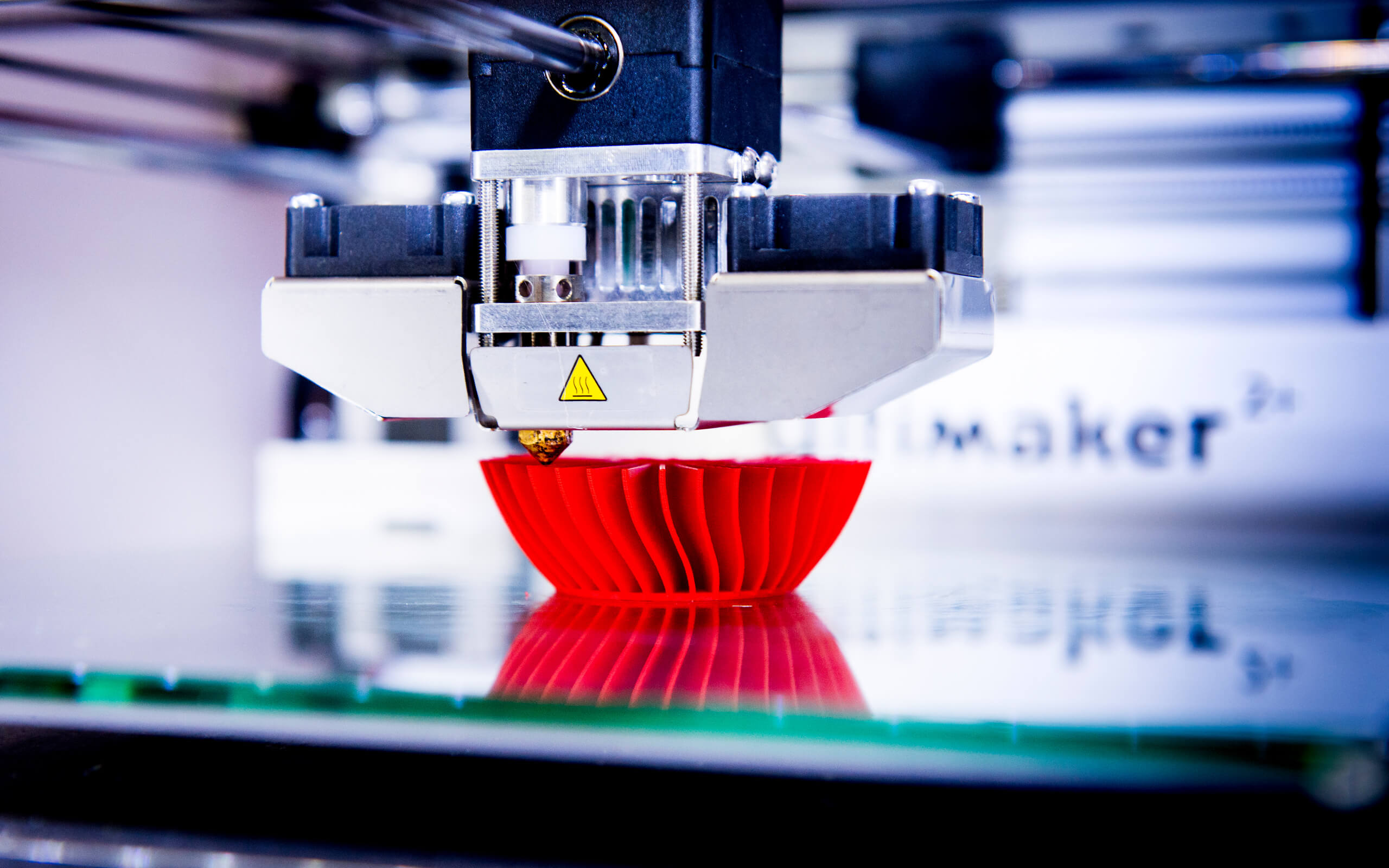 3D printing machine creating a red case