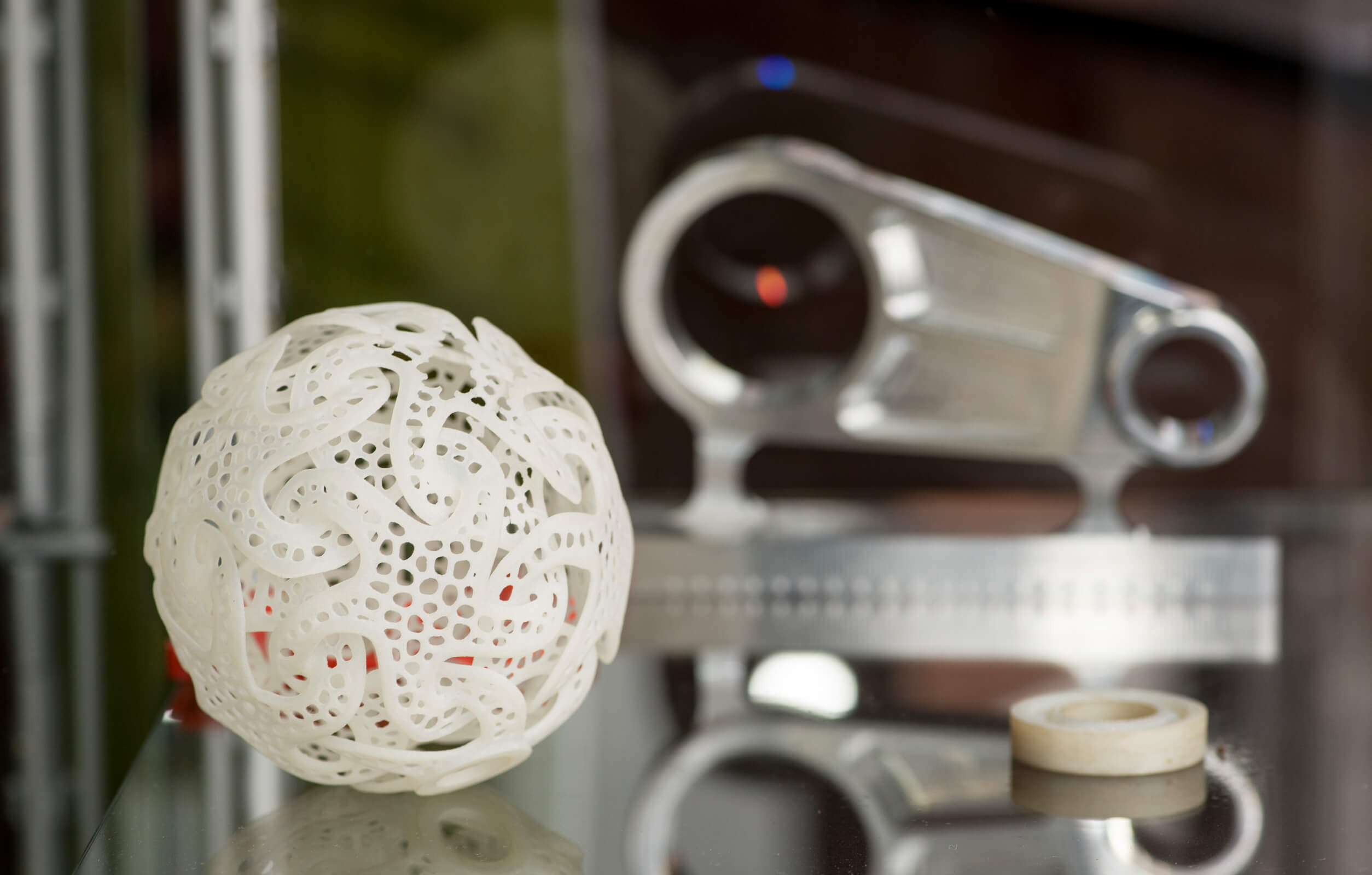 image of a 3d ball of lace and a machine that has created it