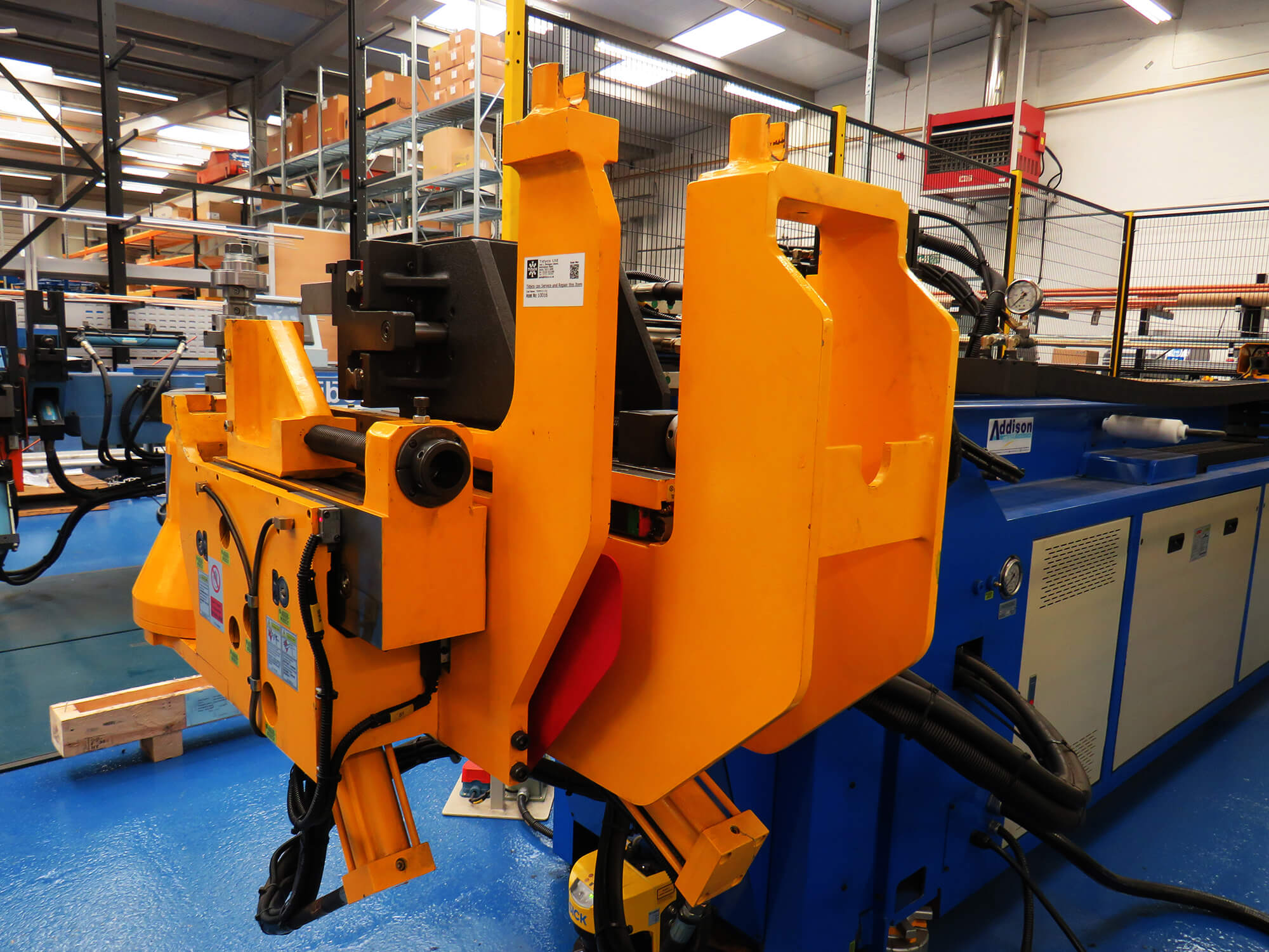 A large orange machine in a factory used to bend products