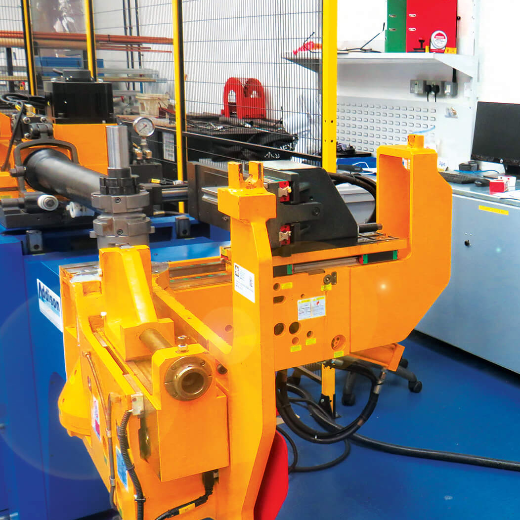 Orange machinery in a factory with a blue floor