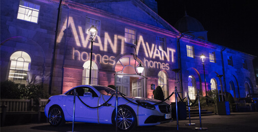 Avant homes at night with a white car in front