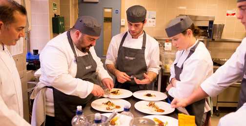 A group of hospitality students and some chefs demonstrating a recipe