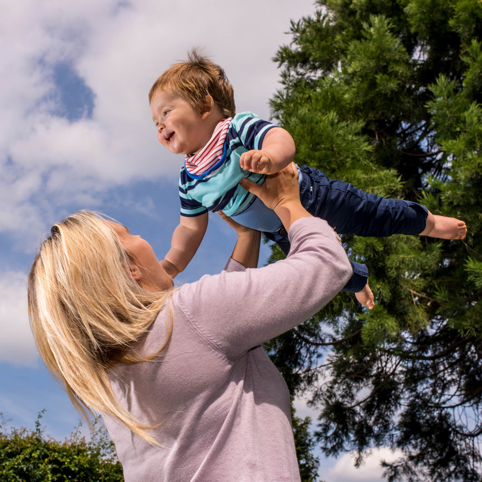 Woman holding child in the air