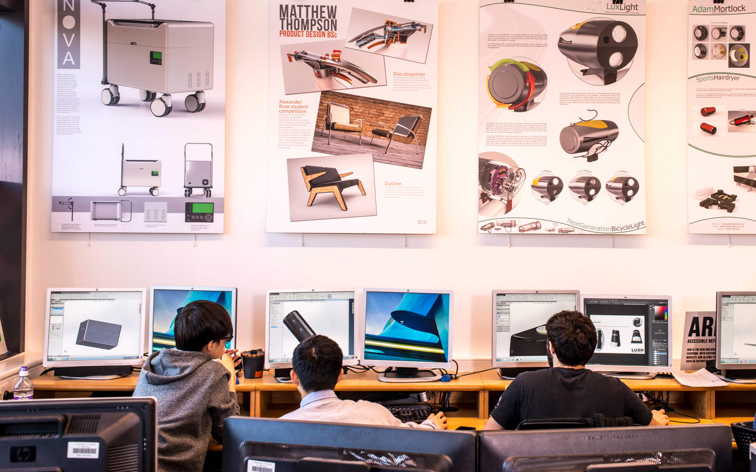 Students working in the product design studio with work displayed on the wall behind them