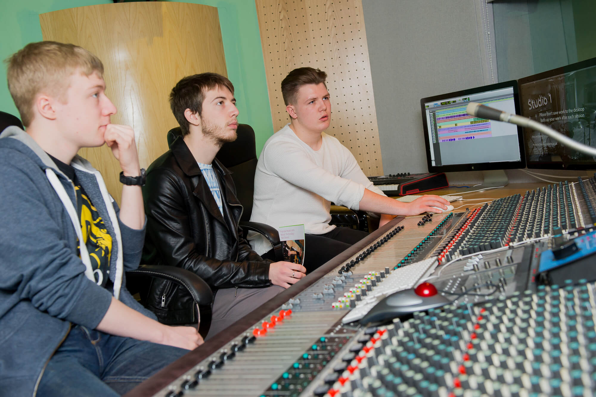 Applicants using the mixing desk in our music studio
