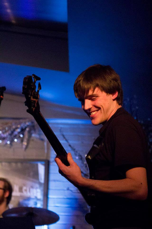 Graduate Tom Bland playing bass guitar