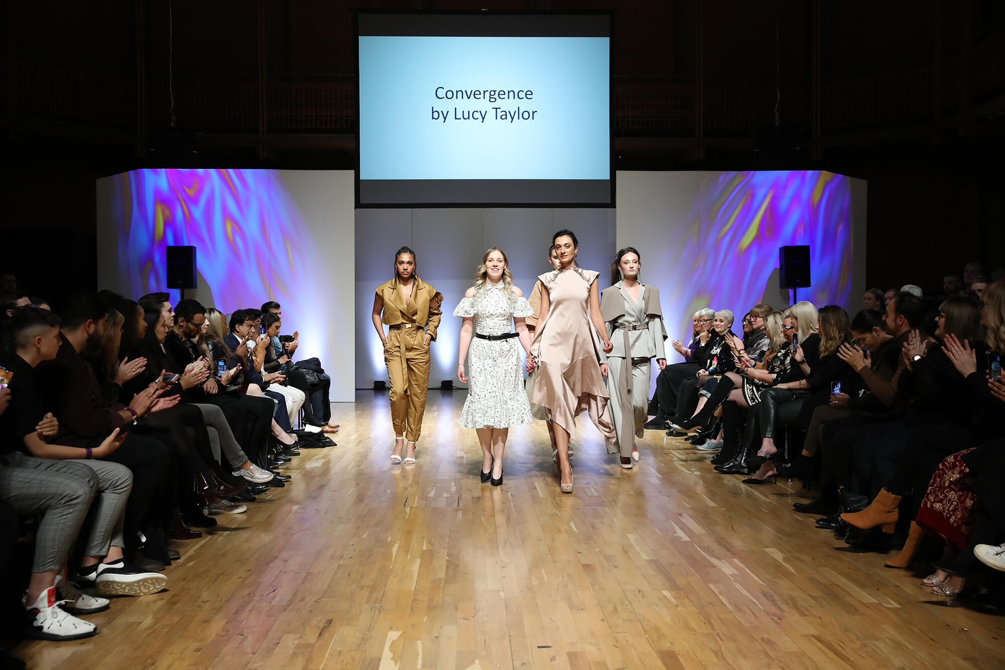 Lucy Taylor walking down a runway with models wearing clothing from 'Convergence', Lucy's winning collection at the Midlands Fashion Awards