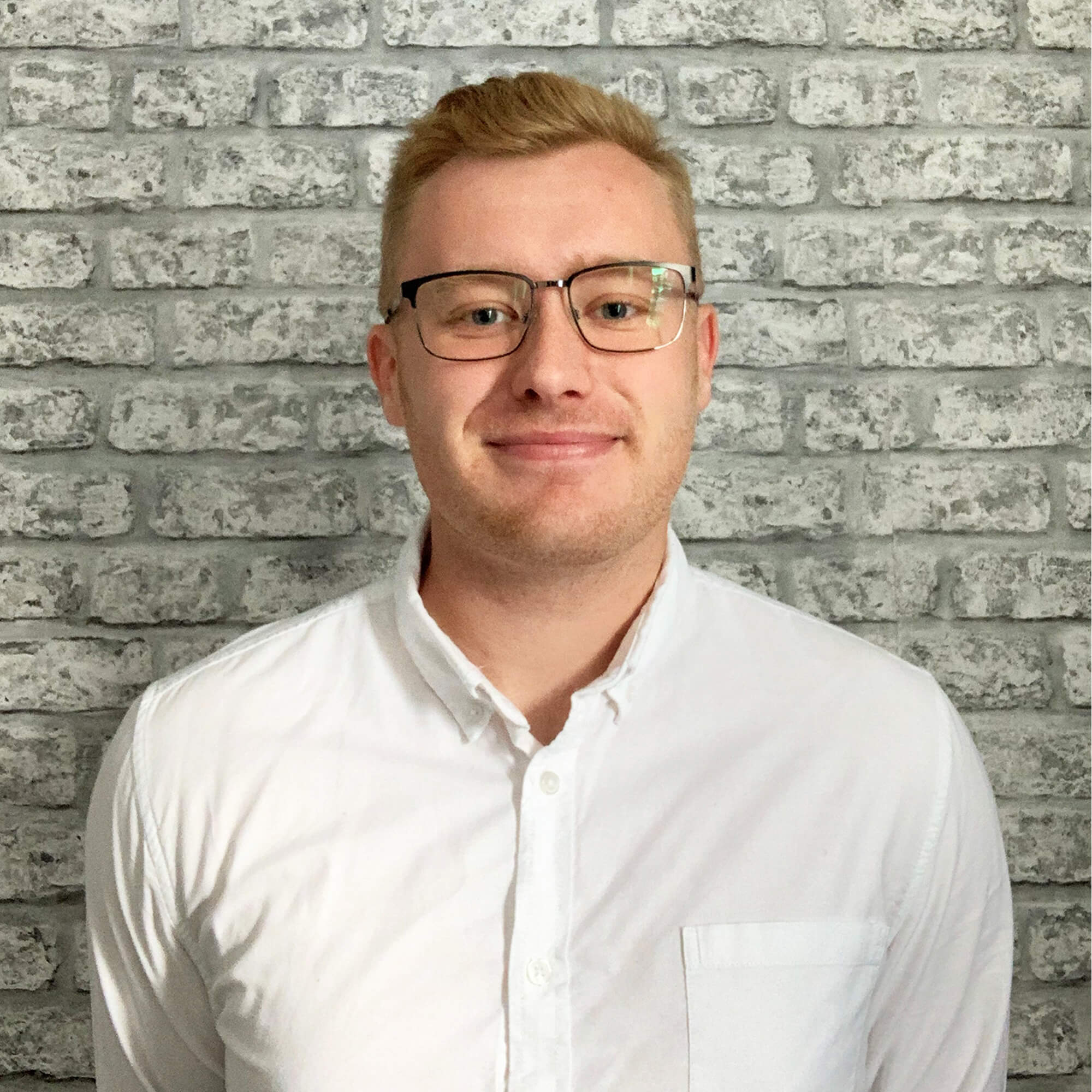 Photo of a blonde male wearing glasses and a white shirt looking at the camera