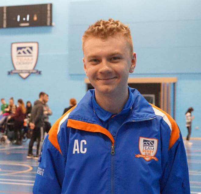Sport and Education student, Adam Cook, wearing a blue Team Derby jacket standing in the sports hall.