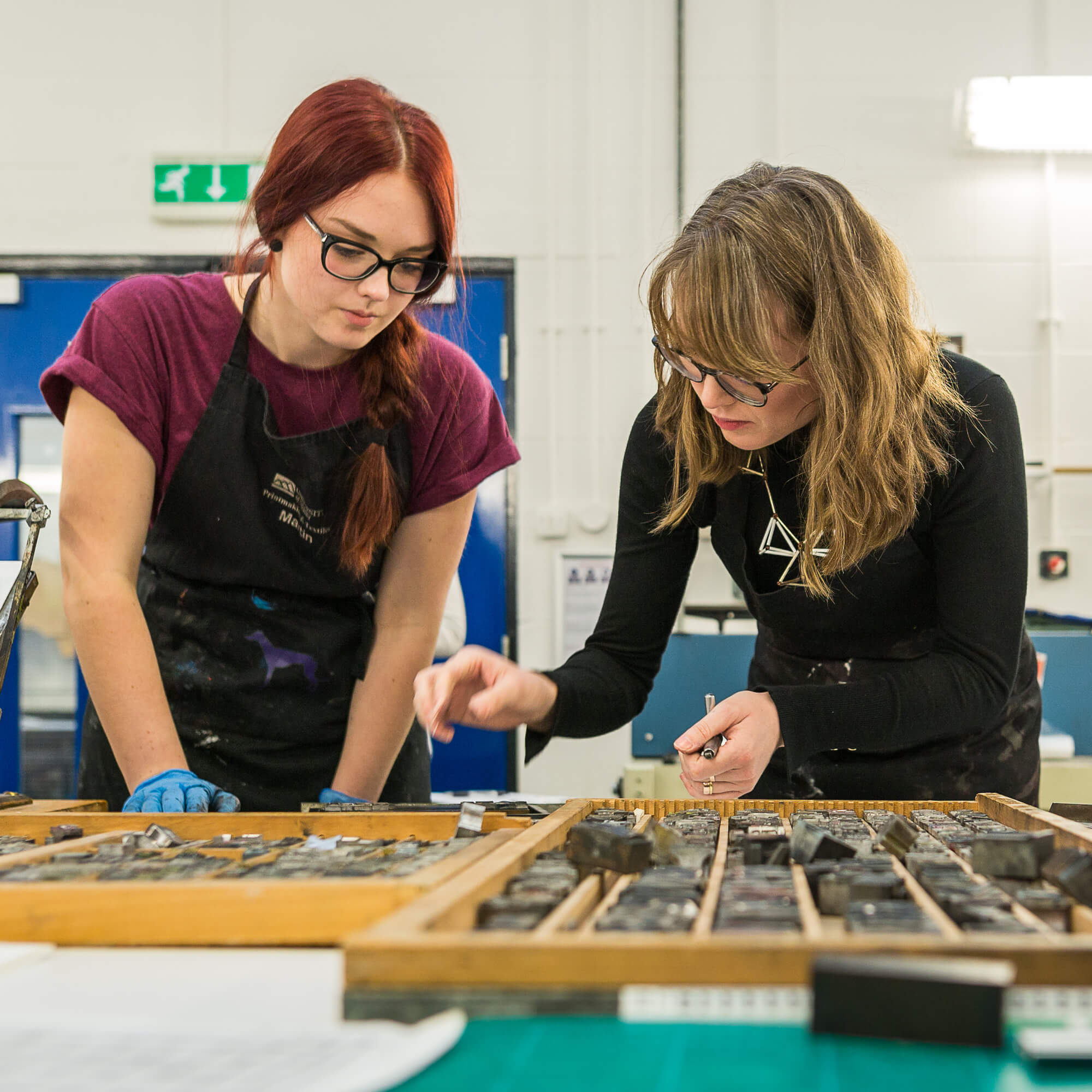 Two female students experiment with letter press tools