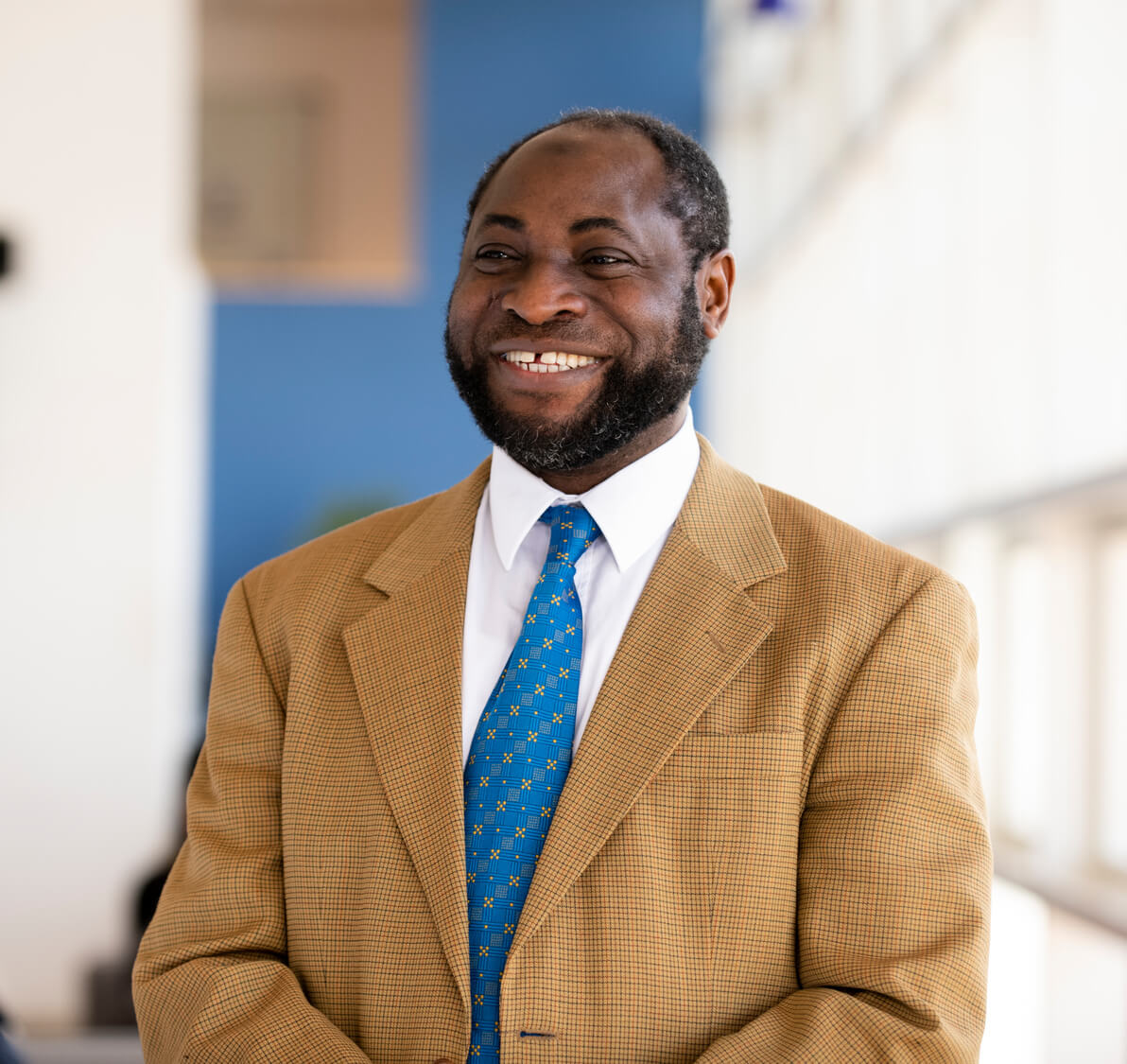 Professor Kamil Omoteso standing, smiling, dressed in a suit with blue tie